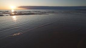 Puesta del sol carmesí con el cielo y el espejo claros como reflexiones en agua - arena y ondas acanaladas - tuja, Letonia - 13  metrajes