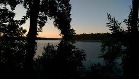 Puesta del sol clara sobre el lago Fotos de archivo libres de regalías