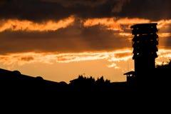 Puesta del sol colorida con la silueta de la chimenea en una casa del tejado encima Imágenes de archivo libres de regalías