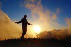 Puesta del sol colorida con una silueta de un adolescente relajado en una pista de senderismo de larga distancia GR131 que lleva  Foto de archivo libre de regalías