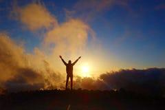 Puesta del sol colorida con una silueta de un adolescente relajado en una pista de senderismo de larga distancia GR131 que lleva  Fotos de archivo libres de regalías