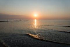 Puesta del sol colorida en el mar con reflexiones y nubes Fotos de archivo