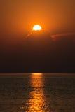 Puesta del sol colorida en el mar con reflexiones y nubes Imagen de archivo