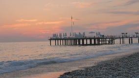 Puesta del sol colorida en el mar Playa guijarrosa hermosa con las ondas y el embarcadero metrajes
