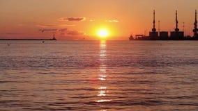 Puesta del sol colorida en el puerto El sol en los sistemas del fondo sobre el horizonte metrajes