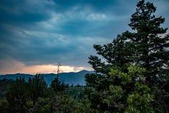 Puesta del sol colorida en las nubes más allá de los árboles de pino foto de archivo libre de regalías