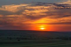 Puesta del sol colorida nublada sobre las colinas y los árboles Imagenes de archivo