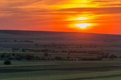 Puesta del sol colorida nublada sobre las colinas y los árboles fotos de archivo