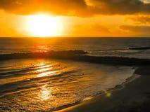 Puesta del sol colorida por el océano y la playa Imagenes de archivo