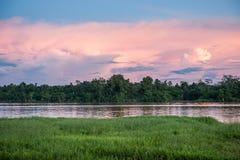 Puesta del sol colorida profundamente en el río en la selva tropical en la isla de Nueva Guinea Río, nubes de la puesta del sol y Foto de archivo