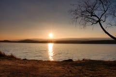 Puesta del sol colorida romántica en el lago Vare con el árbol de abedul y Sun rojo caliente en espejo del agua Fotos de archivo libres de regalías