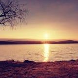 Puesta del sol colorida romántica en el lago Vare con el árbol de abedul y Sun rojo caliente en espejo del agua Fotografía de archivo