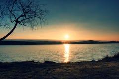 Puesta del sol colorida romántica en el lago Vare con el árbol de abedul y Sun rojo caliente en espejo del agua Fotos de archivo