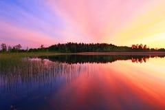 Puesta del sol colorida sobre el agua Imagenes de archivo