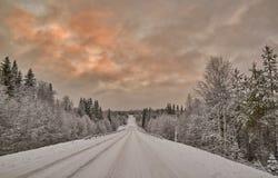Puesta del sol colorida sobre el camino finlandés Foto de archivo libre de regalías