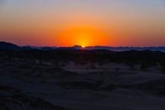 Puesta del sol colorida sobre el desierto de Namib, Namibia, África Montañas, dunas y silueta de los árboles del acacia en contra Fotos de archivo