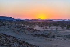 Puesta del sol colorida sobre el desierto de Namib, Namibia, África Montañas, dunas y silueta de los árboles del acacia en contra Imagenes de archivo