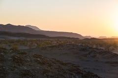 Puesta del sol colorida sobre el desierto de Namib, Namibia, África Montañas, dunas y silueta de los árboles del acacia en contra Foto de archivo libre de regalías