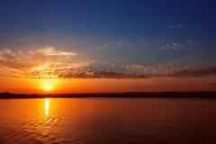 Puesta del sol colorida sobre el lago Foto de archivo
