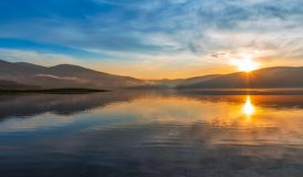 Puesta del sol colorida sobre un lago de la monta?a imagenes de archivo