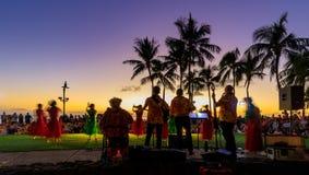 Puesta del sol colorida tropical con la silueta de la orquesta y de las palmeras en la playa de Waikiki foto de archivo libre de regalías