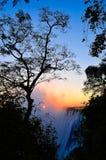 Puesta del sol con el árbol sobre la cascada Imagenes de archivo