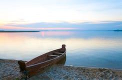 Puesta del sol con el barco cerca de la orilla del lago del verano Fotografía de archivo