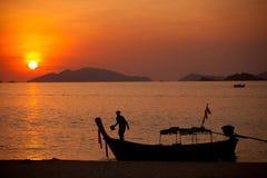 Puesta del sol con el barco del pescador Fotos de archivo