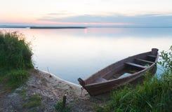 Puesta del sol con el barco viejo de la inundación en orilla del lago del verano Imagen de archivo libre de regalías