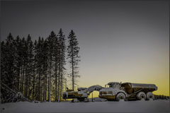 Puesta del sol con el cavador y el camión Fotografía de archivo libre de regalías