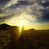 Puesta del sol con el cielo dramático sobre el campo de un granjero Foto de archivo libre de regalías
