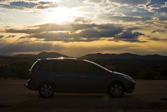 Puesta del sol con el coche en silueta Imagen de archivo libre de regalías