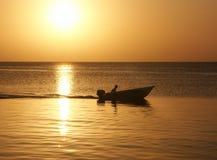 Puesta del sol con el hombre en barco Imagenes de archivo
