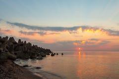 Puesta del sol con el sol y los rayos de sol en el mar Imágenes de archivo libres de regalías