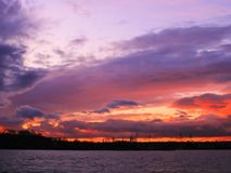 Puesta del sol con horizonte el flamear en el campo y opinión sobre el agua fotografía de archivo