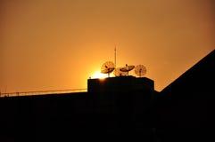 Puesta del sol con la antena de plato Imagen de archivo libre de regalías