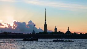 Puesta del sol con la fortaleza de Peter y de Paul, St Petersburg, Rusia Naves en el río de Neva almacen de video