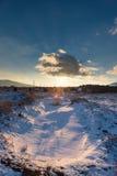 Puesta del sol con la nube sobre el sol, campo nevoso Fotografía de archivo libre de regalías