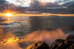 Puesta del sol con la onda en rocas Imagen de archivo