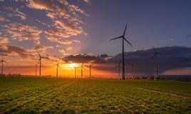 Puesta del sol con la opinión sobre las turbinas de viento fotografía de archivo libre de regalías