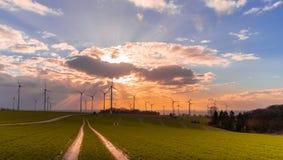 Puesta del sol con la opinión sobre las turbinas de viento imagen de archivo libre de regalías