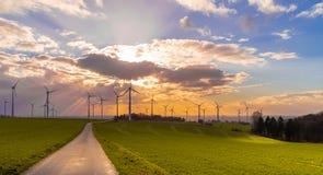 Puesta del sol con la opinión sobre las turbinas de viento imagenes de archivo