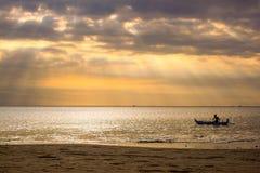 Puesta del sol con la opinión y el barco solo en Bali, Indonesia del mar fotografía de archivo