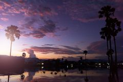 Puesta del sol con la pequeñas charca y palmeras Fotografía de archivo libre de regalías