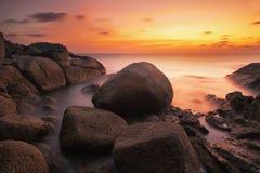 Puesta del sol con la roca y la playa Fotos de archivo