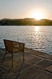 Puesta del sol con la silla cerca del lago Imágenes de archivo libres de regalías
