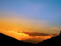 Puesta del sol con la silueta de la montaña Fotos de archivo libres de regalías