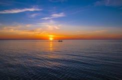 Puesta del sol con la silueta del barco Imagen de archivo