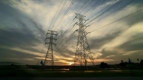 Puesta del sol con la torre de la línea eléctrica de dos transmisiones en campo de arroz
