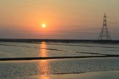 Puesta del sol con las cosechas del agua salada Imagen de archivo